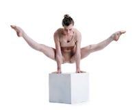 Ung nätt akrobat som poserar med kuben i studio Fotografering för Bildbyråer