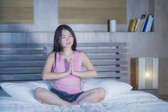 Ung nätt asiatisk kinesisk kvinna20-tal eller avslappnande hemmastatt sovrumsammanträde för 30-tal på säng i namasteyogaposition  royaltyfri bild