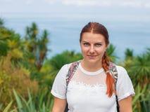 Ung nätt attraktiv kvinnlig med rött hår som omkring ser och att gå på gatan av den tropiska staden med palmträd som är solig royaltyfri bild