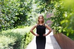 Ung nätt blond flicka i halv tillväxt med akimbo händer Royaltyfria Foton