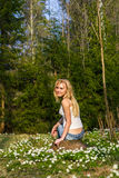Ung nätt blond kvinna på en äng med blommor Arkivfoton
