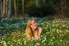 Ung nätt blond kvinna på en äng med blommor Arkivbilder