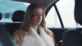 Ung nätt blondin som kör i bilmaskinskrivningen på hennes smartphone som meddelar med vännen av henne arkivfilmer