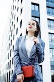 Ung nätt brunettaffärskvinna som poserar mot modern byggnad, livsstilfolkbegrepp Fotografering för Bildbyråer