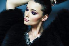 Ung nätt brunettflicka med att posera för modemakeup som är elegant i pälslag med smycken på blå bakgrund, livsstil royaltyfria bilder