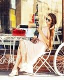 Ung nätt brunettkvinna, når att ha shoppat sammanträde på kafét utanför på att le för gata arkivfoto