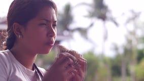 Ung nätt dam som äter hamburgaren lager videofilmer