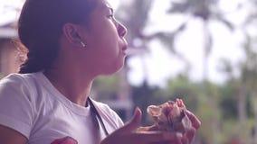 Ung nätt dam som äter hamburgaren arkivfilmer