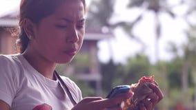 Ung nätt dam som äter hamburgaren, medan genom att använda den smarta telefonen arkivfilmer