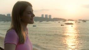 Ung nätt drömlik kvinna i rosa t-skjorta på cityscape för fartyg för strandhavssolnedgång på bakgrund stock video