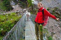 Ung nätt flicka för stående som bär röda omslagsslingaberg Trekking landskap för berg Laddade djura åsnor för husvagn Royaltyfria Foton