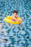Ung nätt flicka i gul simningcirkel i pöl med klar wat royaltyfria bilder