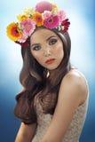 Ung nätt flicka med blommahatten Royaltyfria Bilder