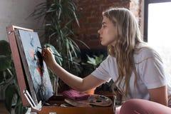 Ung nätt flicka med borsten och palett som sitter nära staffliteckningsbild Konst kreativitet, hobby som drar process royaltyfri bild