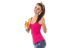 Ung nätt flicka med den nya orange coctailen för härliga leendedrinkar som ler på kamera och visar tummar som upp isoleras på Arkivfoto