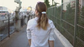 Ung nätt flicka som går på bakgrunden av härliga stadslandskap lager videofilmer