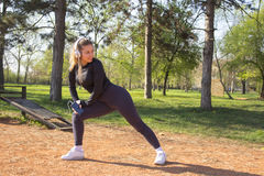 Ung nätt flicka som gör övning och spring i parkera Royaltyfri Bild