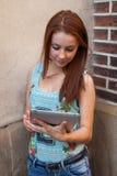 Ung nätt flicka som gör on-line shopping genom att använda minnestavlan Urban bac Arkivfoto