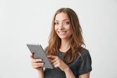 Ung nätt flicka som ler se kameran som surfar rengöringsduken som bläddrar internet på minnestavlan över vit bakgrund Arkivbild