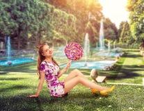 Ung nätt flicka som rymmer en enorm färgrik lollypop Fotografering för Bildbyråer