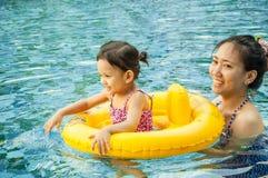 Ung nätt flicka som spelar i gul simningcirkel med hennes mothe royaltyfri bild