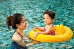 Ung nätt flicka som spelar i gul simningcirkel med hennes mothe fotografering för bildbyråer
