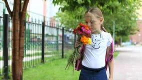 Ung nätt flicka som står nära skola med solig dag för ryggsäck och för blommor tillbaka skola till Skolflickan går att studera Arkivbilder