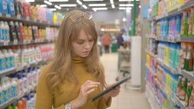 Ung nätt flickashopping i stormarknad och information om söka efter om produkterna på hennes minnestavla stock video