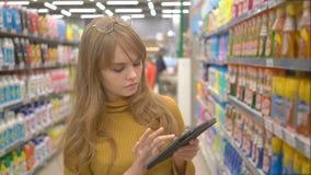Ung nätt flickashopping i stormarknad och information om söka efter om produkterna på hennes minnestavla arkivfilmer