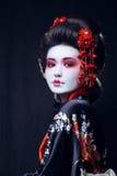 Ung nätt geisha i kimono med sakura och arkivfoton