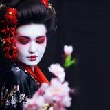 Ung nätt geisha i kimono med sakura och garnering royaltyfria bilder