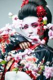 Ung n?tt geisha i svart kimono bland sakura, asiatisk ethnocloseup arkivbilder