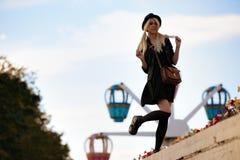 Ung nätt hipsterflicka som är utomhus- i solig dag, bärande tillfällig clothiershatt royaltyfria foton