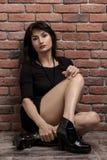 Ung nätt kvinna i den mörka korta klänningen nära tegelstenväggen arkivbilder