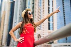 Ung nätt kvinna i den röda klänning- och sugrörhatten som pekas med händer på i stadens centrum skycrapers i modern stad Lowen me royaltyfri foto