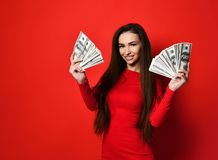 Ung nätt kvinna i den röda klänningen som döljer bak grupp av pengarsedlar royaltyfria bilder