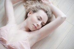 Ung nätt kvinna i försiktig damunderkläder som ligger på golvet Nära övre stående för skönhet av den kvinnliga framsidan med natu Arkivbilder