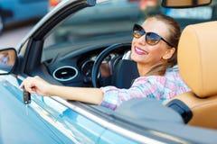 Ung nätt kvinna i solglasögon som sitter i wi för en cabrioletbil Fotografering för Bildbyråer
