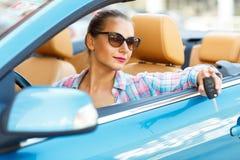 Ung nätt kvinna i solglasögon som sitter i wi för en cabrioletbil Royaltyfri Bild