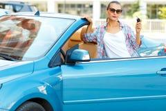 Ung nätt kvinna i solglasögon som står nära cabrioleten med Royaltyfria Bilder
