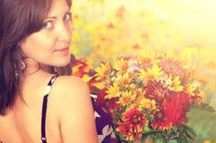 Ung nätt kvinna med blommor fotografering för bildbyråer