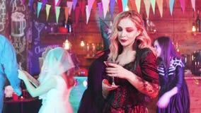 Ung nätt kvinna med ett exponeringsglas av blod i hennes handdans på ett halloween parti arkivfilmer