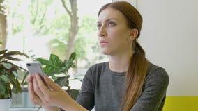 Ung nätt kvinna med hästsvanssammanträde, i kafé, hållande mobil och att se telefonen, allvarligt och bekymrat arkivfilmer