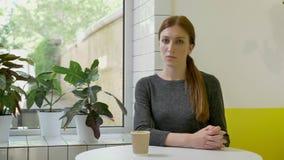 Ung nätt kvinna med hästsvanssammanträde i kafé och att se rakt in camera, korsade händer, allvarligt och bekymrat stock video