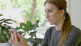 Ung nätt kvinna med hästsvanssammanträde i kafét som rymmer telefonen och tänker, beslutsamt och bekymrat arkivfilmer