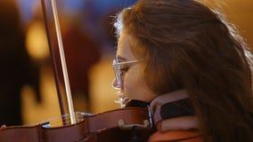 Ung nätt kvinna med lockigt hår som spelar fiolen i gångtunnel lager videofilmer