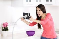 Ung nätt kvinna som är chockad och ser ipad arkivfoton