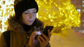 Ung nätt kvinna som använder smartphonen i staden på natten Royaltyfria Foton
