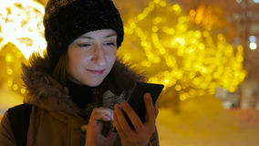Ung nätt kvinna som använder smartphonen i staden på natten Royaltyfri Bild