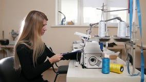 Ung nätt kvinna som arbetar med symaskinen på fabrik lager videofilmer